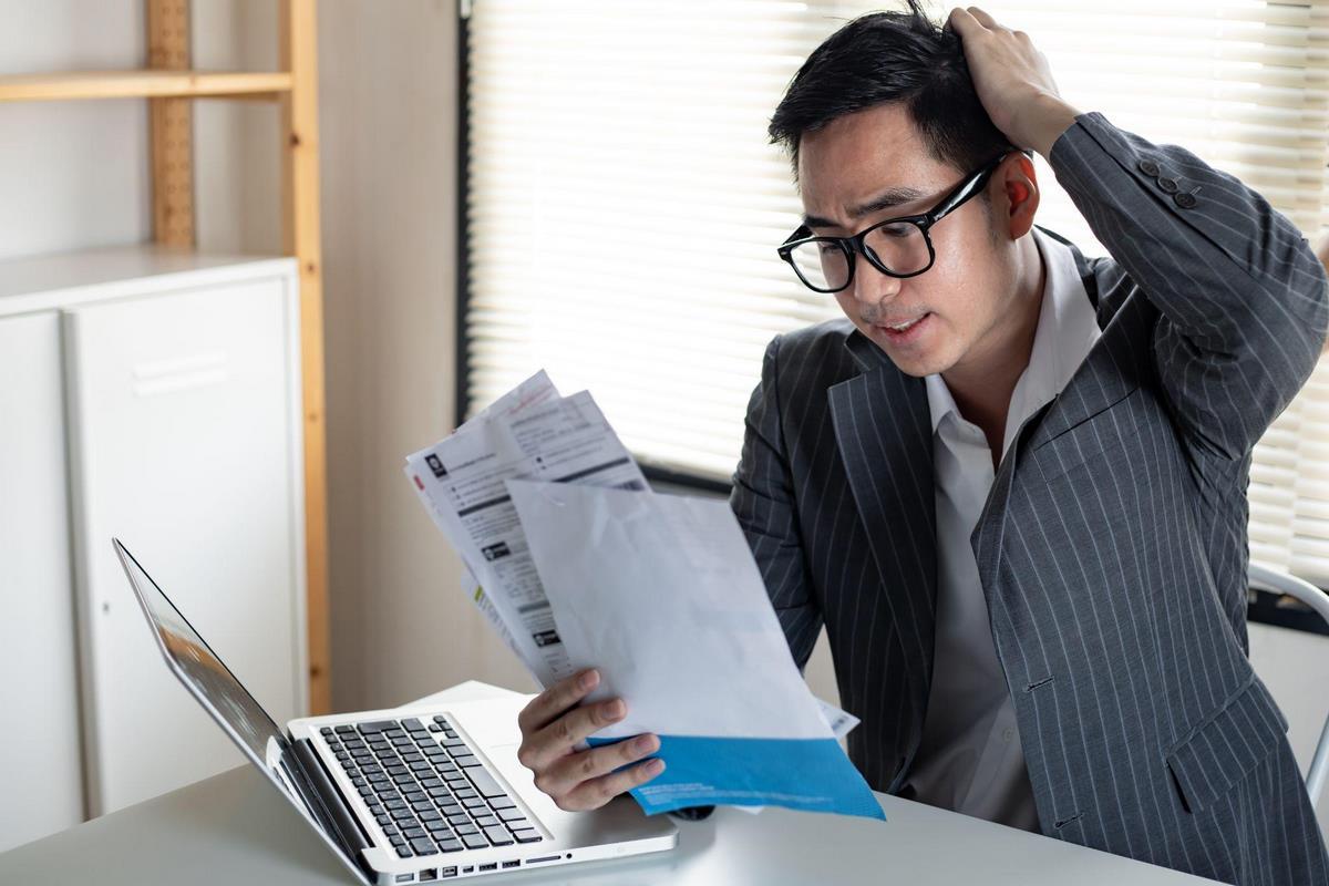 Человек с документами перед компьютером